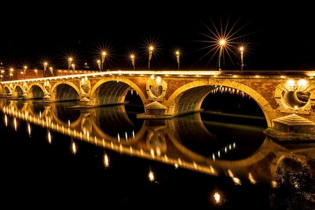 Puente pont neuf iluminado por la noche. una pequeña parte de la iluminación está rota. hermoso reflejo en el río garona. toulouse, francia