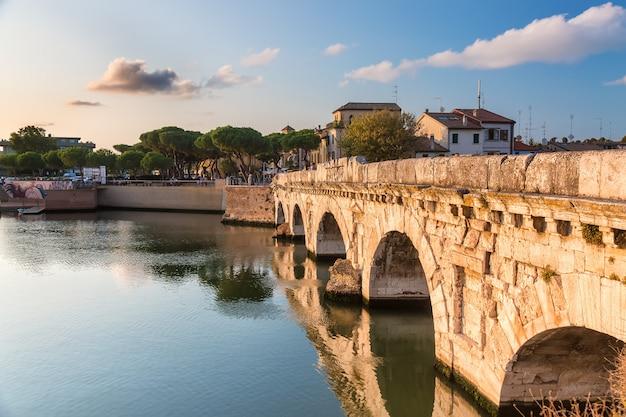 Puente romano histórico de tiberio sobre el río marecchia durante la puesta de sol en rimini, italia.