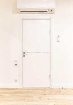 Puerta blanca en casa moderna con aire acondicionado y piso de madera.