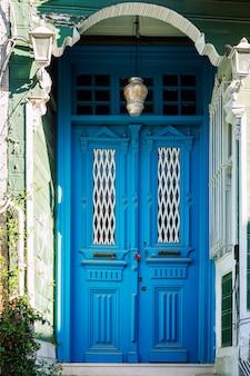 Puerta cerrada doble azul con una casa antigua. de cerca. vertical.