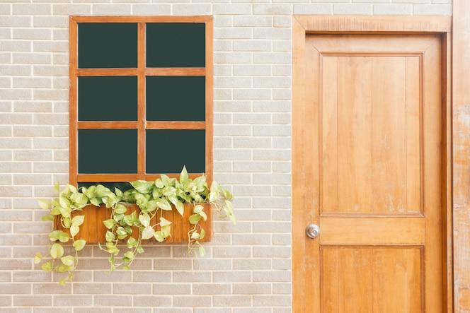 Puerta de madera de una casa. vista frontal de una puerta frontal de madera en una casa amarilla con reflejos en la ventana y una amplia vista del porche y pasarela frontal. tiro horizontal.