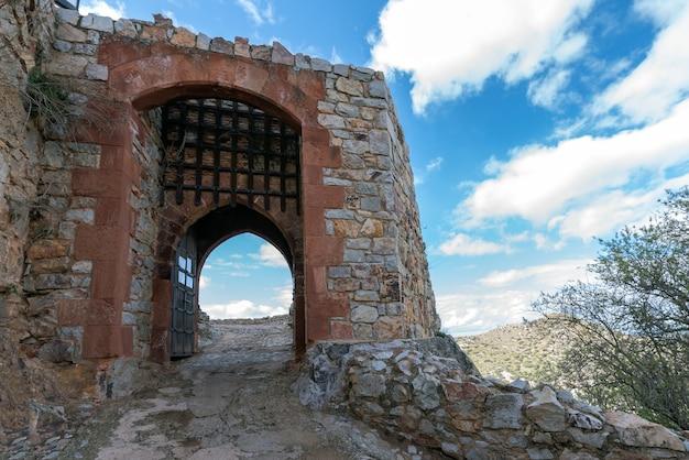 Puerta de entrada abierta a un castillo con las rejas levantadas