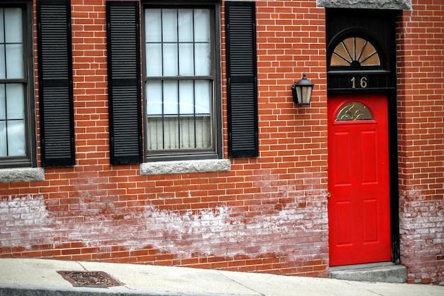 Puerta de entrada roja a un edificio de ladrillo que muestra el número dieciséis en una calle con ventanas de vidrio