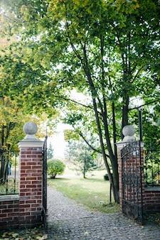 Puerta de hierro forjado negro de diseño clásico en un hermoso jardín verde