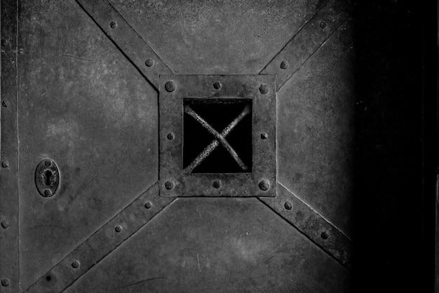 Puerta de hierro vieja, oxidada y pesada