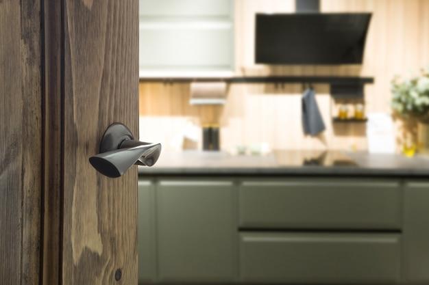 Puerta de madera abierta y vista a la cocina moderna.