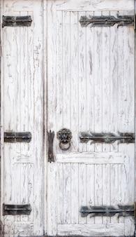 Puerta de madera blanca en mal estado con bisagras forjadas y una manija en forma de anillo de cabeza de león