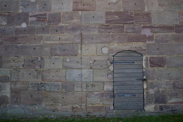 Una puerta de madera contra un muro de piedra. camina cerca del castillo