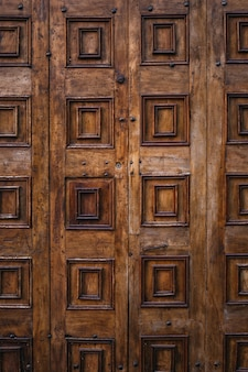 Puerta de madera marrón de una iglesia en italia con decoraciones talladas