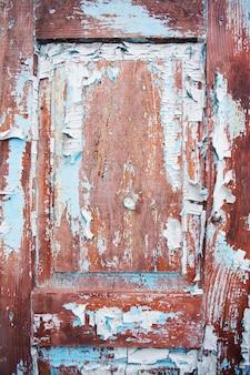 Puerta de madera muy antigua con pintura azul agrietada.