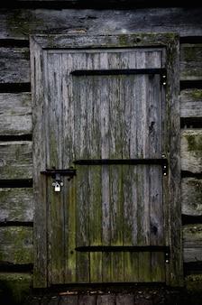 Puerta de madera de una sombría casa abandonada