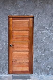 Puerta de madera en la textura de la pared de hormigón