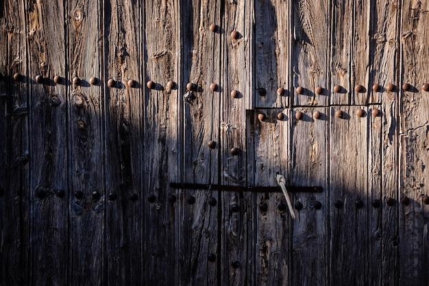 Puerta de madera vieja y decrépita, medio iluminada por el sol, en una zona rural despoblada.