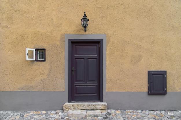Puerta de madera vieja en la pared amarilla concreta del viejo estilo rústico del mundo con la pequeña ventana en el lado