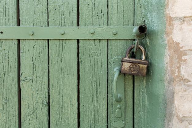Puerta de madera vieja con peeling y pintura verde agrietada.