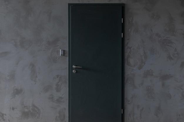Puerta metálica con señalización en muro de hormigón gris.