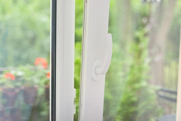 Puerta de plástico blanca abierta de vidrio a la terraza del balcón