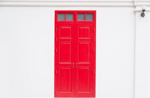 Puerta roja tradicional de madera de un viejo en la pared blanca, en tailandia