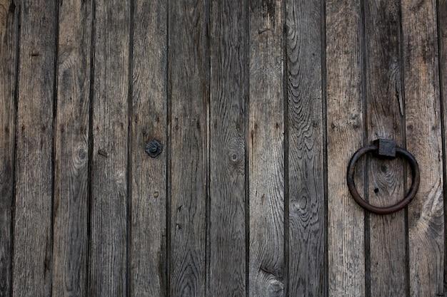 Puerta rural de madera antigua con asa de anillo de metal