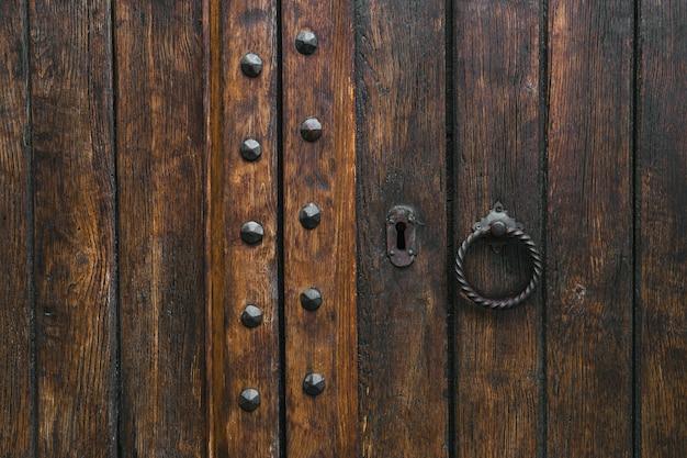 Puerta rústica antigua de madera envejecida de la puerta del marrón oscuro con el golpeador del metal.