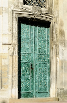 Puertas dobles verdes antiguas con adornos dorados