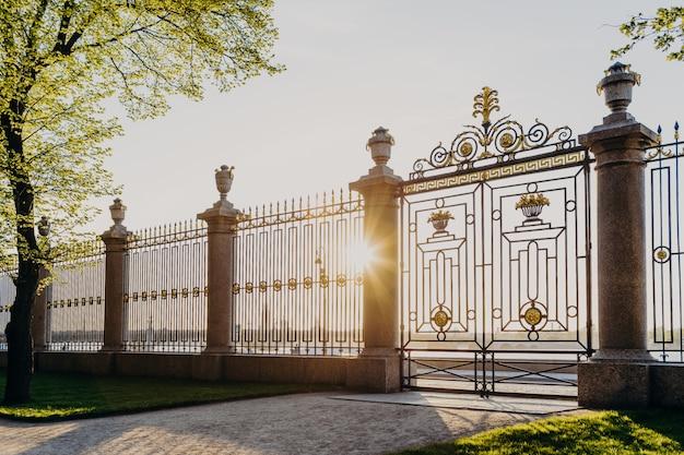 Puertas del jardín de verano en rusia, san petersburgo. soleado día de primavera. hermosos árboles verdes y hierba