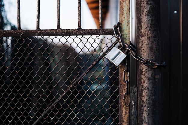 Puertas con malla en cerradura en valla de hierro. la puerta de metal con rejilla está fortificada con refuerzo diagonal.