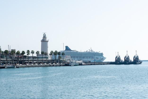Puerto de málaga con el faro y el crucero de pasajeros al fondo.
