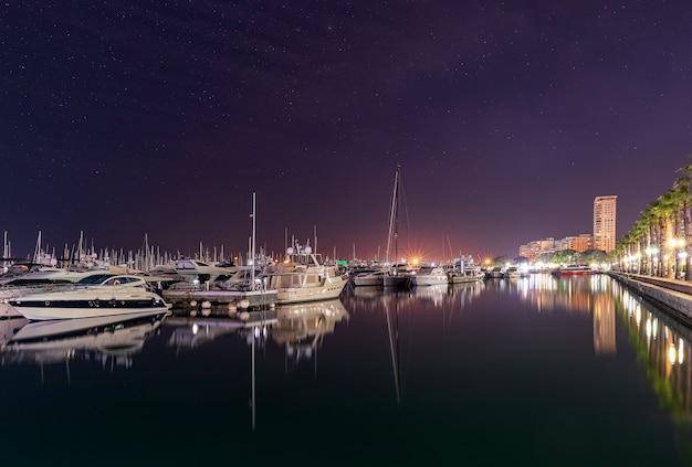 Puerto marítimo de alicante en la noche con yates de lujo, barcos y barcos de pesca están parados en filas en el puerto