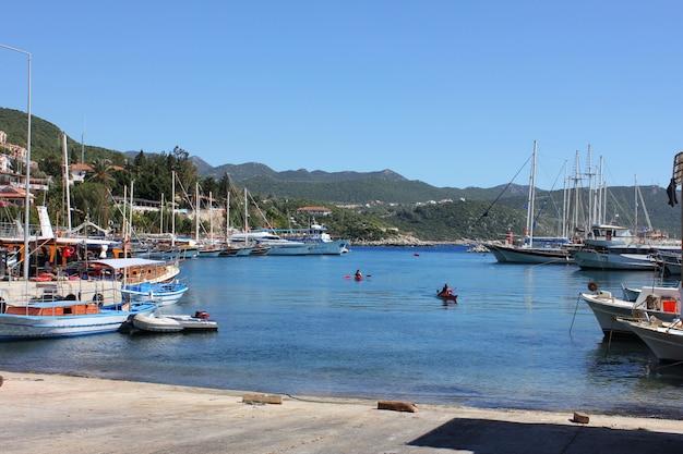 Puerto de yates en la pintoresca laguna mediterránea. gente en kayaks