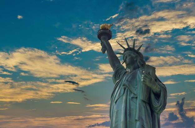 Puesta de sol aérea con la estatua de la libertad en manhattan, ciudad de nueva york, ee.