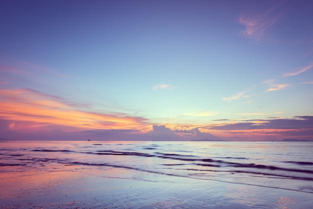 Puesta del sol azul rosada tropical hermosa y nubes amarillas