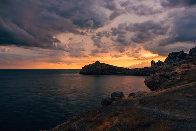 Puesta de sol de color en el telón de fondo de montañas y mar