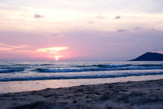 Puesta del sol colorida de la playa del océano con los rayos anaranjados azules profundos del cielo y del sol.