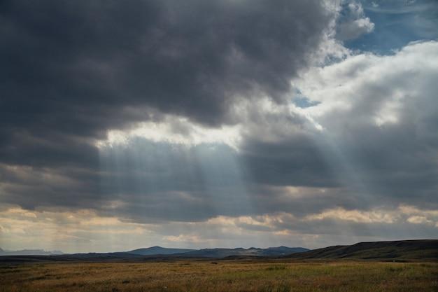 Puesta de sol en el desierto, los rayos del sol brillan a través de las nubes. meseta de ukok de altai