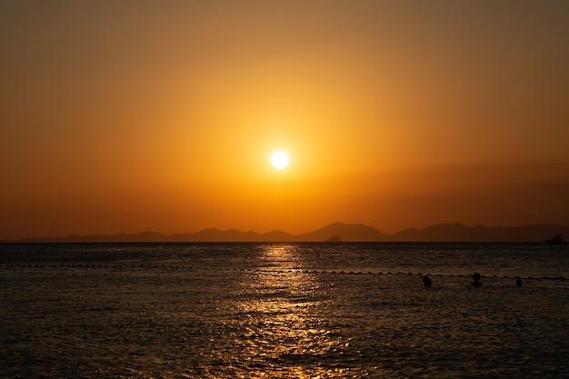 Puesta de sol dorada sobre las líneas de la montaña del mar en el fondo gente nadando en el agua