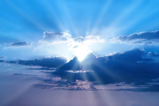 La puesta de sol es un hermoso cielo azul con rayos de sol y nubes