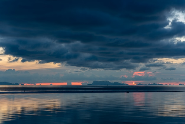 Puesta de sol espectacular gran nube de lluvia tropical cielo azul y mar