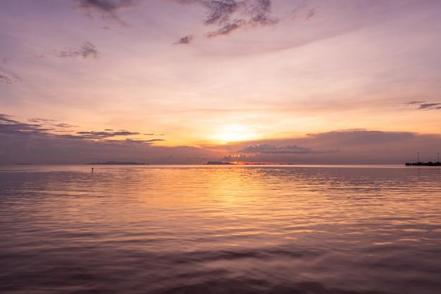 Puesta del sol hermosa de la playa con el fondo ligero de oro de la nube del cielo del mar