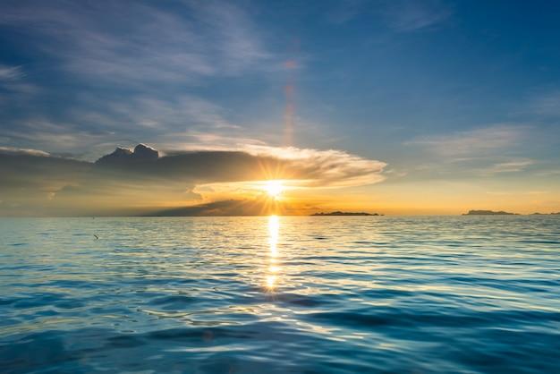 Puesta del sol hermosa de la playa con el mar azul y el fondo ligero de oro de la nube del cielo