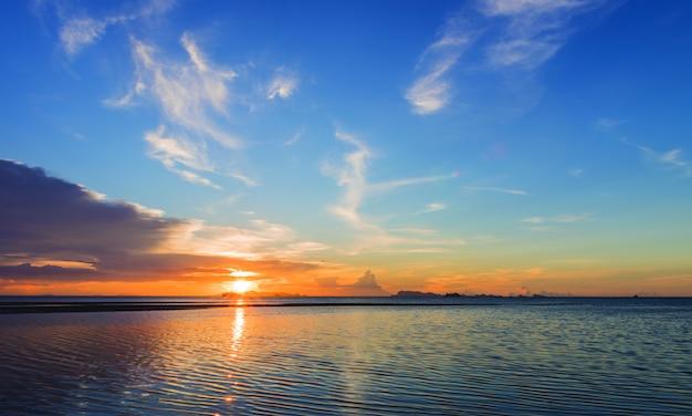 Puesta del sol hermosa de la playa con las nubes de lluvia grandes y el fondo de oro del cielo ligero