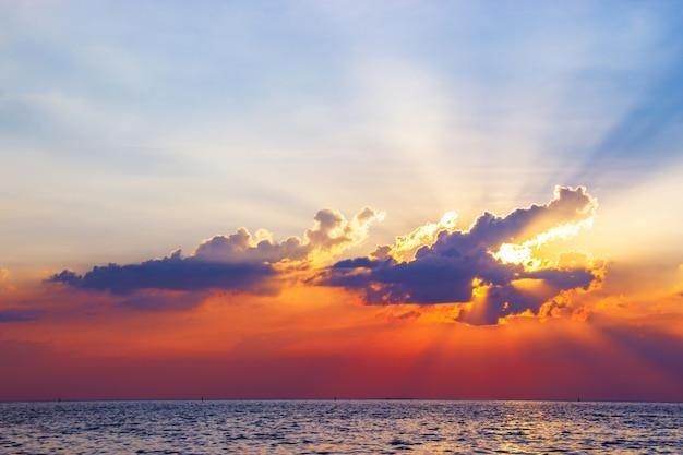 La puesta del sol hermosa sobre el mar reflejó en crepúsculo colorido del agua superficial.