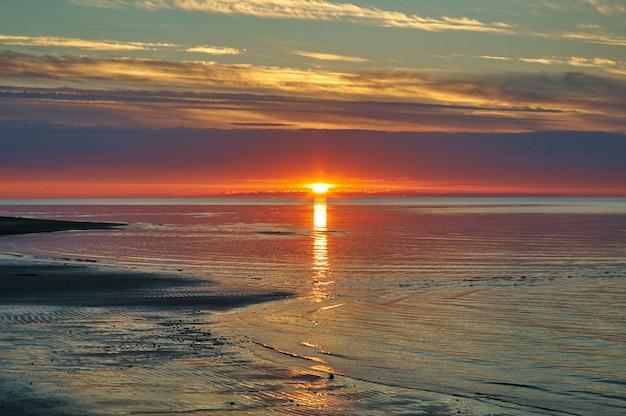 Puesta de sol del mar blanco, rusia costa arenosa de la costa sur