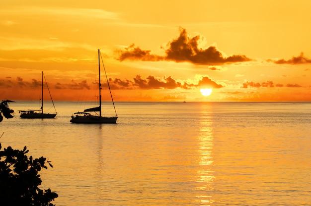 Puesta de sol en el mar y la silueta del yate de vela