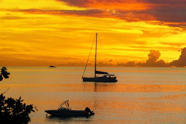 Puesta de sol en el mar y la silueta de yates de vela con un hermoso paisaje del caribe, la isla de santa lucía