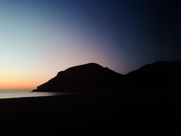 Puesta de sol con una montaña de silueta en la playa