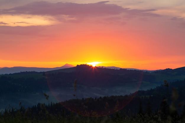 Puesta de sol en las montañas de los cárpatos. el sol se pone detrás de una cadena montañosa. hermosas nubes multicolores en el cielo de la tarde.