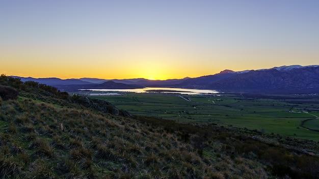 Puesta de sol en las montañas con lago de agua en el valle y rayos de sol en el cielo azul. navacerrada madrid. españa.