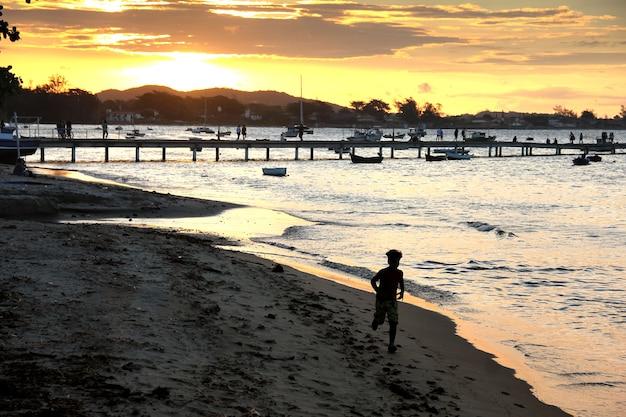 Puesta de sol en el muelle, niño corriendo hacia la cámara, imagen retroiluminada