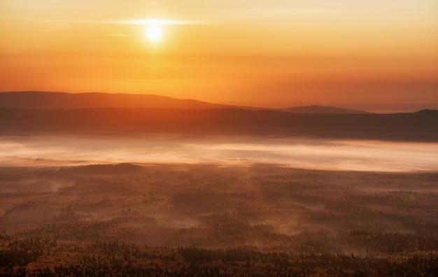 Puesta de sol naranja con el sol en el horizonte poniéndose.